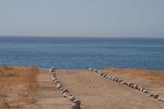 Chemin rayé par pierre sur la plage Photos libres de droits