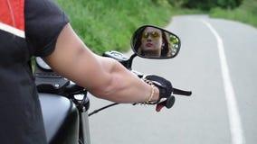 CHEMINEMENT de la réflexion dans le miroir de vue arrière, beau cycliste de femelle adulte en verres sans casque Vue arrière Au r clips vidéos