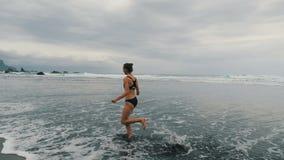 Cheminement du tir de la jeune femme attirante pulsant sur la plage orageuse de Benijo dans T?n?rife, les ?les Canaries Coureur f clips vidéos