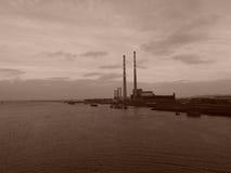 Cheminées d'évacuation des fumées le long de Dublin Harbor dans la sépia Images stock