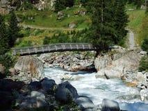 Chemins et ponts en bois sur le courant de Chärstelenbach dans la vallée alpine de Maderanertal image stock