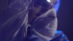 Chemische arbeider die beschermend masker zetten vóór experiment in geheim laboratorium stock footage