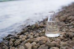 Chemische fles met water, meer of rivier op de achtergrond stock foto's