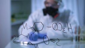Chemische formule op glasraad, wetenschapper die in gasmasker op achtergrond schrijven stock videobeelden