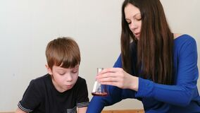 Chemische Reaktion mit Abgasemission in der Flasche mit roter Flüssigkeit Mutter und Sohn, die Chemie tun stock video footage