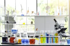 Chemisches flüssiges Reagenzglas und Mikroskop im Labor stockbilder