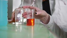 Chemisches Labor Die junge Frau, die ein Experiment macht, versucht verschiedene chemische Reaktionen stock footage
