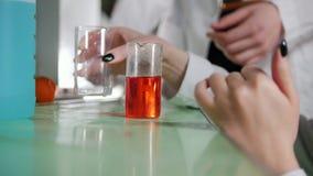 Chemisches Labor Junge Frau, die ein Experiment, mischende Flüssigkeiten, suchend nach Reaktion macht stock video
