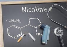 Chemisches Nikotin der Formel geschrieben und mit Kreide auf eine Tafel, nahe bei einem Inhalator und einem Stethoskop gezeichnet stockfotos