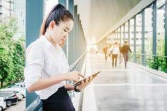 Chemise blanche de port asiatique de femme d'affaires utilisant le smartphone pour l'OE Photos stock