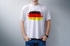 Chemise blanche de port d'homme avec la copie de drapeau de l'Allemagne Images stock