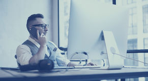 Chemise blanche de port, gilet et travail de jeune homme d'affaires barbu à l'ordinateur de bureau dans le grenier moderne Homme  images libres de droits
