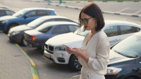 Chemise blanche de port de jeune femme heureuse utilisant le téléphone portable et le sourire sur la rue près de la route avec de banque de vidéos