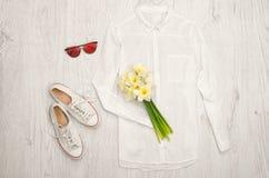 Chemise blanche, verres, espadrilles et un bouquet des jonquilles Fond en bois concept à la mode Photos stock