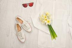 Chemise blanche, verres, espadrilles et un bouquet des jonquilles Fond en bois concept à la mode Images stock