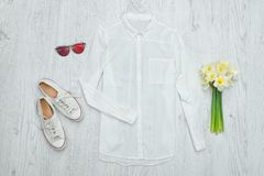 Chemise blanche, verres, espadrilles et un bouquet des jonquilles Woode Images stock
