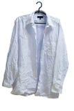 Chemise blanchie par blanc masculin froissée sur le cintre Images stock