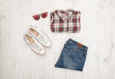 Chemise de plaid, verres, espadrilles et jeans rouges et blancs Fond en bois Concept à la mode, vue supérieure Image libre de droits