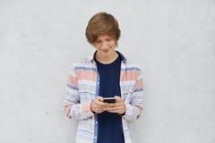 Chemise de port d'adolescent à la mode, tenant le téléphone portable dans des mains, transmission de messages avec des amis ou jo photos libres de droits