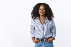 Chemise de port d'afro-américain de coupe de cheveux bouclée attrayante gaie charismatique de femme jugeant des poches de mains s image stock