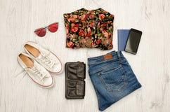 Chemise en fleurs, verres, espadrilles, jeans, téléphone et passeport Fond en bois concept à la mode Images stock