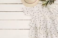 Chemise femelle, chapeau de paille, ananas, points de polka Vieux fond en bois blanc Photographie stock libre de droits