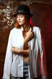 Chemise masculine de port et chapeau de belle jeune femme, posant avec la lumière rouge image libre de droits