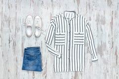 Chemise rayée blanche et bleue, espadrilles blanches et jeans fashiona Image libre de droits