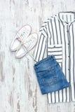 Chemise rayée blanche et bleue, espadrilles blanches et jeans fashiona Photo libre de droits