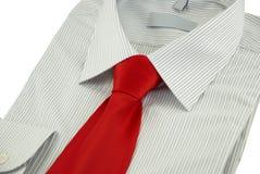 Chemise rayée neuve avec la cravate en soie rouge au-dessus du blanc Image stock