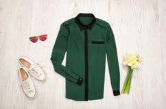 Chemise verte, verres, espadrilles et un bouquet des jonquilles Fond en bois concept à la mode Images stock