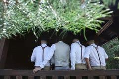 Chemises blanches d'amis d'hommes reposant ensemble la maison de seuil Photos libres de droits