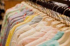 Chemises colorées du ` s de femmes sur des cintres dans un magasin de détail Concept de mode et d'achats Photographie stock libre de droits