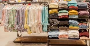 Chemises colorées du ` s de femmes sur des cintres dans un magasin de détail Concept de mode et d'achats Images libres de droits