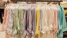 Chemises colorées du ` s de femmes sur des cintres dans un magasin de détail Concept de mode et d'achats Images stock