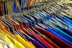 Chemises colorées sur des cintres réglés sur le support à la vente dans le magasin Images stock