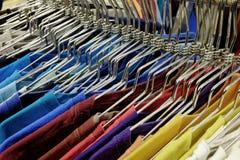 Chemises colorées sur des cintres réglés sur le support à la vente dans le magasin Photos libres de droits