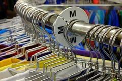 Chemises colorées sur des cintres réglés sur le support à la vente dans le magasin Image libre de droits