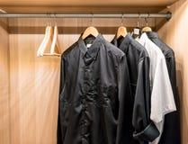Chemises de base noires accrochant dans le cabinet image stock