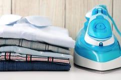 Chemises et fer sur la table Photographie stock libre de droits