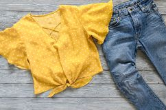 Chemisier de jaune de l'habillement des femmes dans le point de polka, blues-jean Fashio Photographie stock