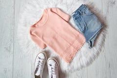 Chemisier rose, shorts de denim et espadrilles sur la fourrure blanche, fond en bois concept à la mode Photos libres de droits