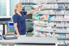 Chemist Arranging Products In Shelves At Pharmacy Stock Photos