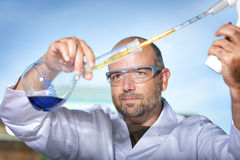 Chemist with blue liquid Royalty Free Stock Images