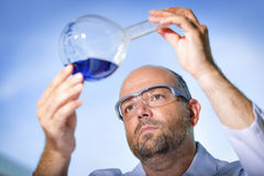 Chemist with blue liquid. Chemist with safety goggles examining a blue liquid Stock Images