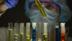 Chemist checking sediment in tube with yellow liquid, substances emitting smoke. Stock footage stock video