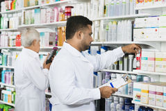 Chemist Counting Stock With Colleague In Pharmacy Stock Images