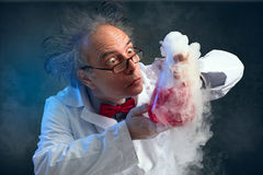 Crazy chemist smelling his experiment stock images