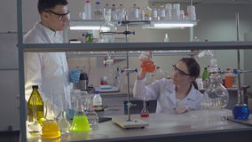 Chemist engineer holding flasks adding liquid to test-tubes with. Diverse team working in laboratory. Professional biologist observed results and discussing stock footage