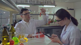 Chemist Engineer holding test tube with liquid talking with student. Adult professional man scientist analyzing medical test or experiments young woman stock video footage